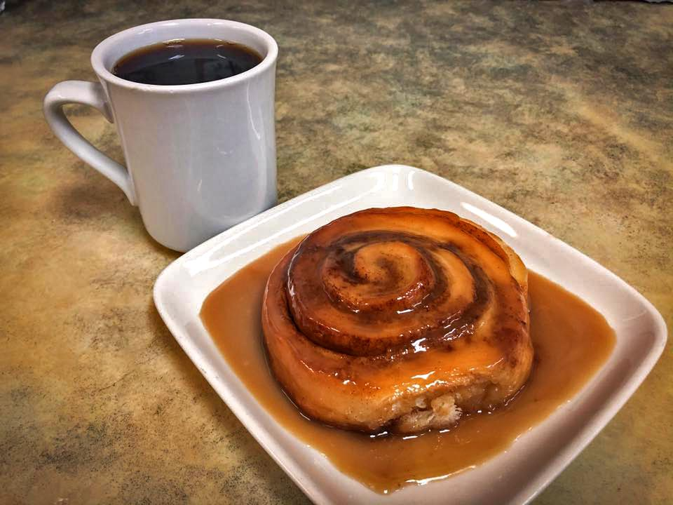 mug filled with coffee and a cinnamon roll on a plate