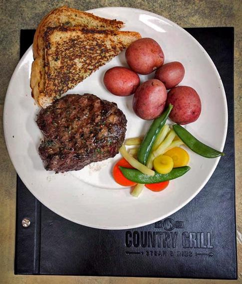 grilled steak with a side of veggies, red potatoes and toast on a plate over a menu