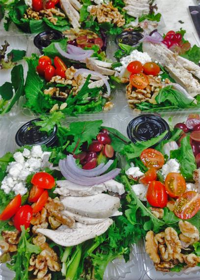 Fresh salads in to-go containers containing onion, tofu, tomatoes, and nuts