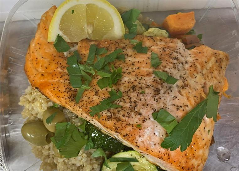 Salmon over brown rice with olives and a lemon wedge