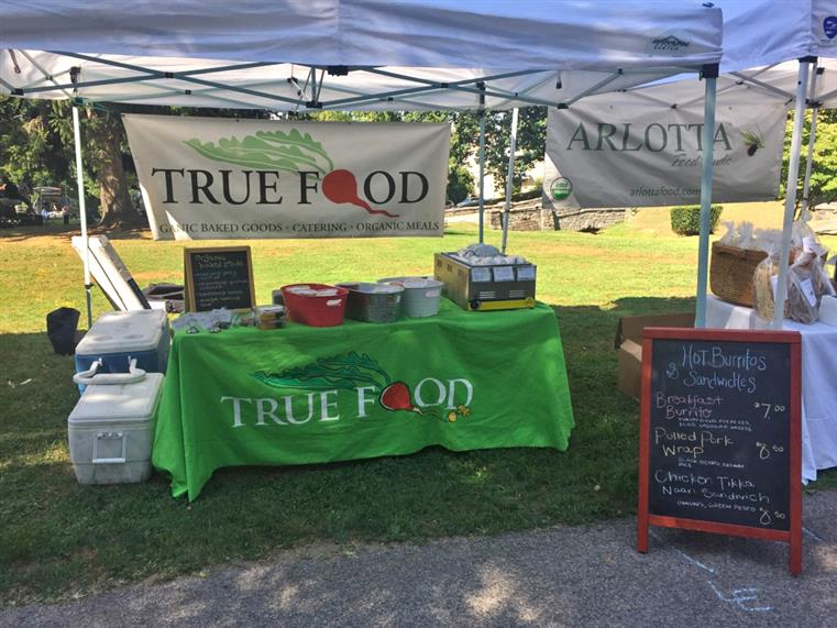 Outdoor True Market table and tent at a seasonal market