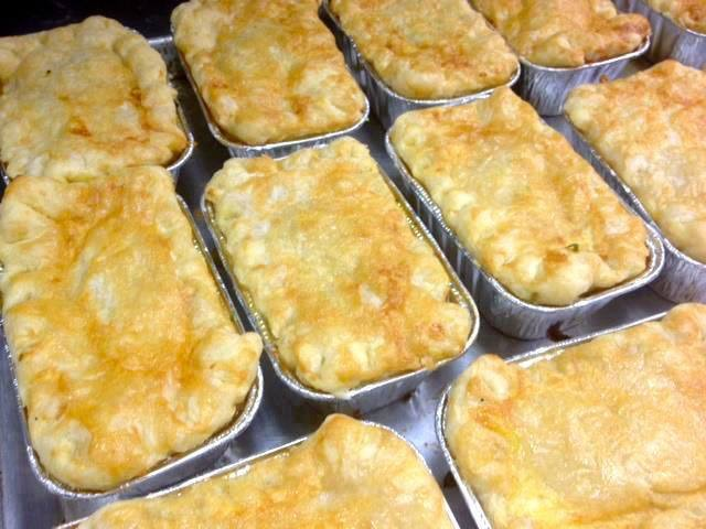 Baked casseroles in trays lined up in rows on a table