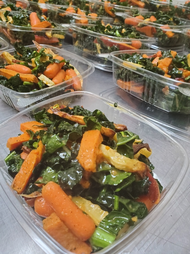 Rows of to-go containers filled with vegetable cold salads
