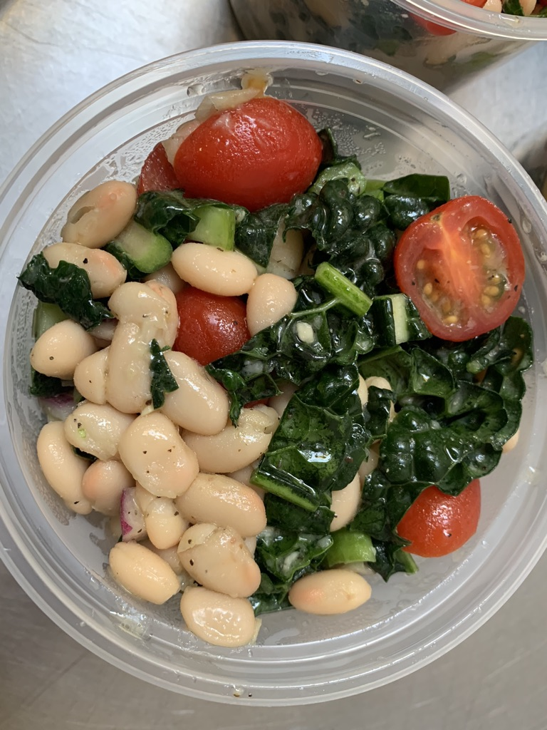 Cannellini beans with leafy greens and cherry tomatoes, topped with a light dressing in a to-go cup