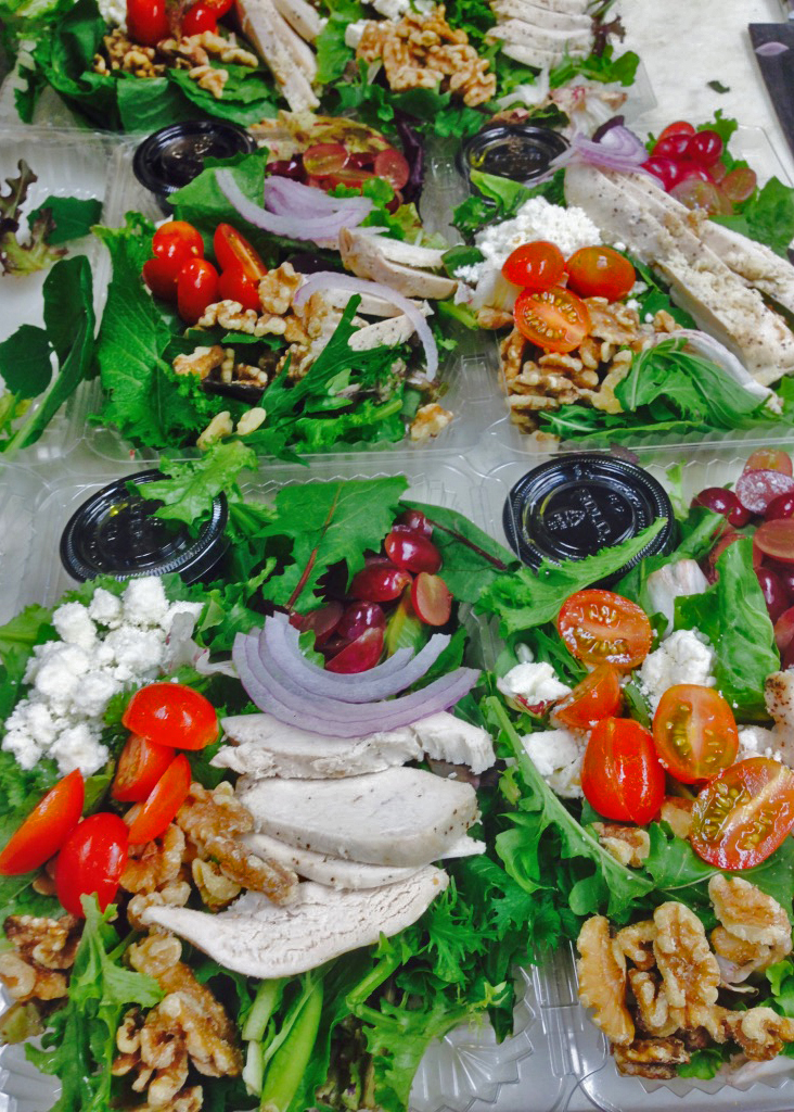 Multiple containers filled with salads, which include tofu, onion, tomatoes, olives, beats, and dressing