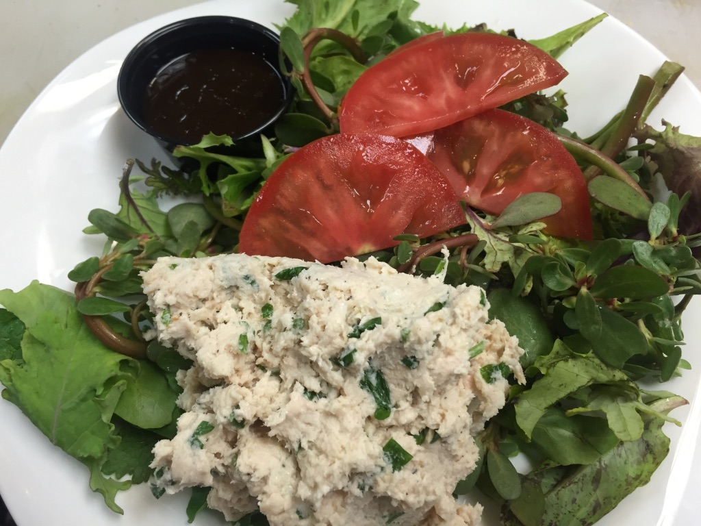 Tuna salad over lettuce with a side of tomato and balsamic dressing