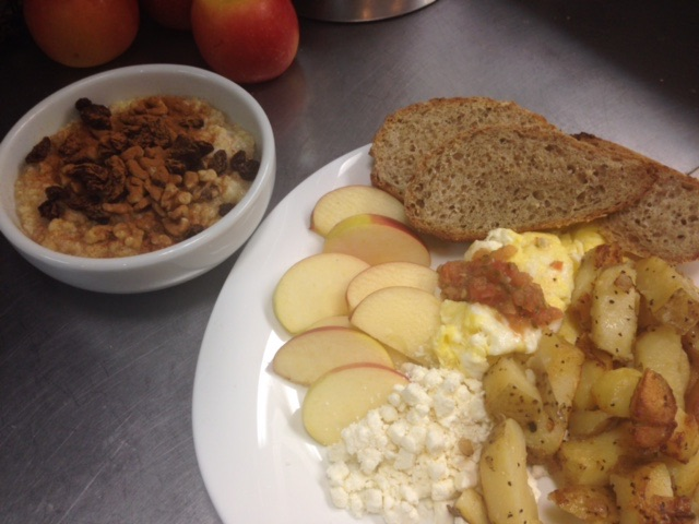 A dish filled with apple slices, toasted bread, scrambled eggs, roasted potatoes, and feta cheese