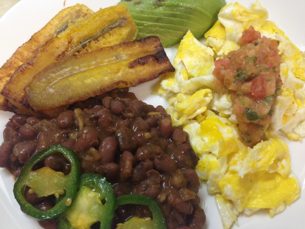 Black beans, plantains, eggs, jalapenos, and avocado on a plate