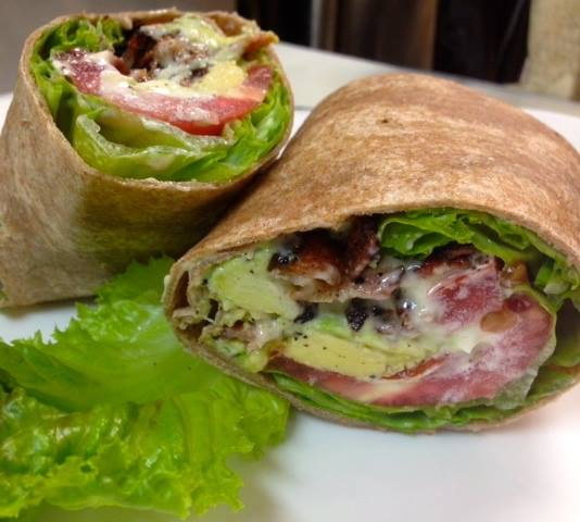 A whole wheat wrap filled with avocado, lettuce, tomato, and bacon