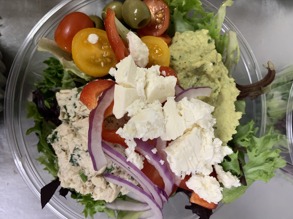 A salad with mesclun greens, topped with feta cheese, tomato, onion, olives, and an avocado spread.