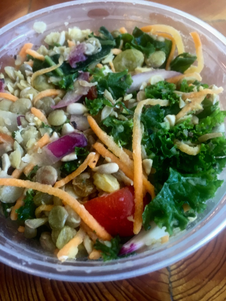 A kale, quinoa, onion, carrot, tomato, and sunflower seed salad
