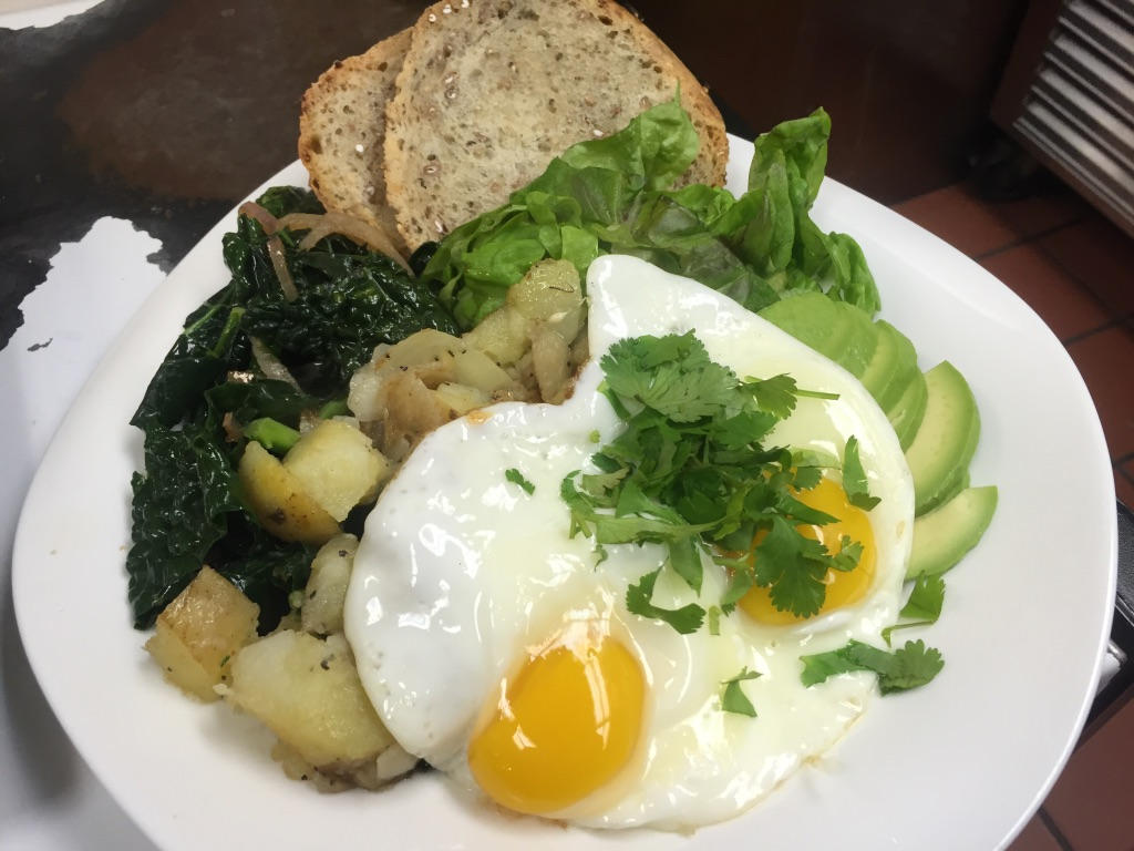 Eggs over avocado, potatoes, lettuce, spinach, and bread