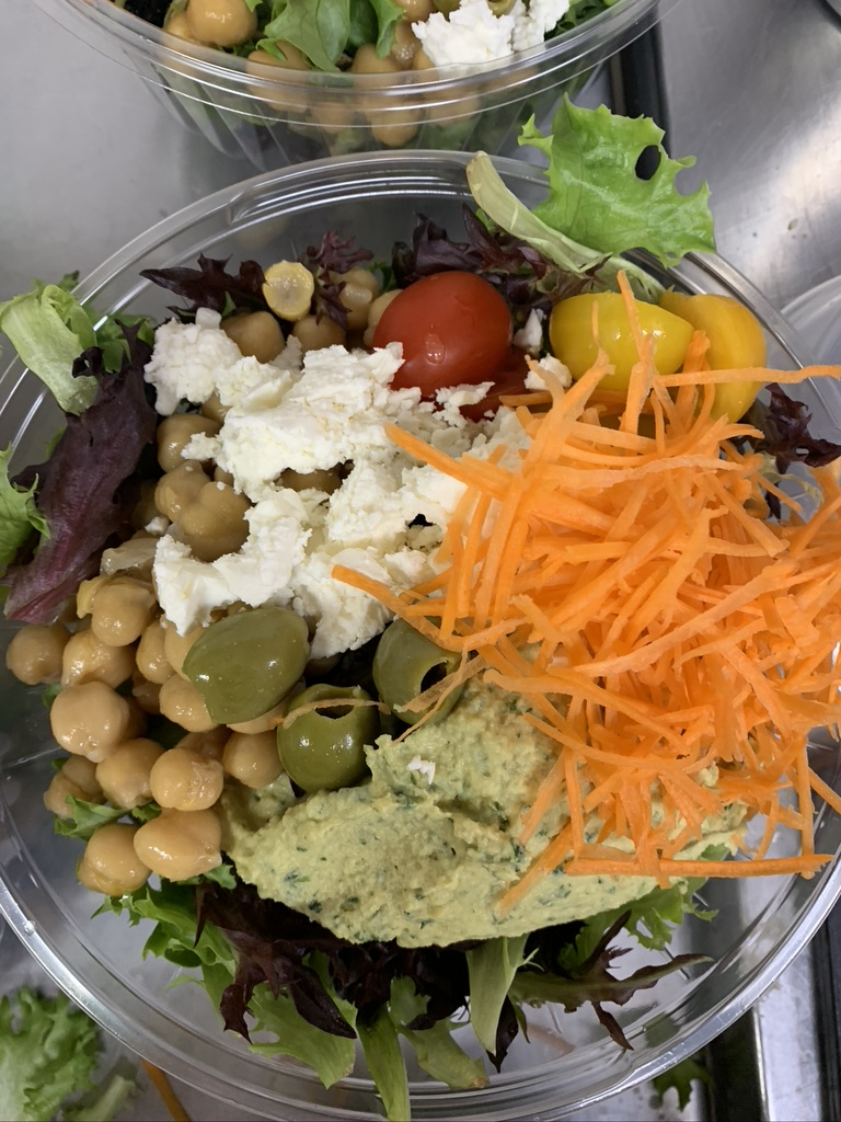 A salad with mesclun greens, topped with shredded carrots, tomatoes, chickpeas, olives, and avocado spread