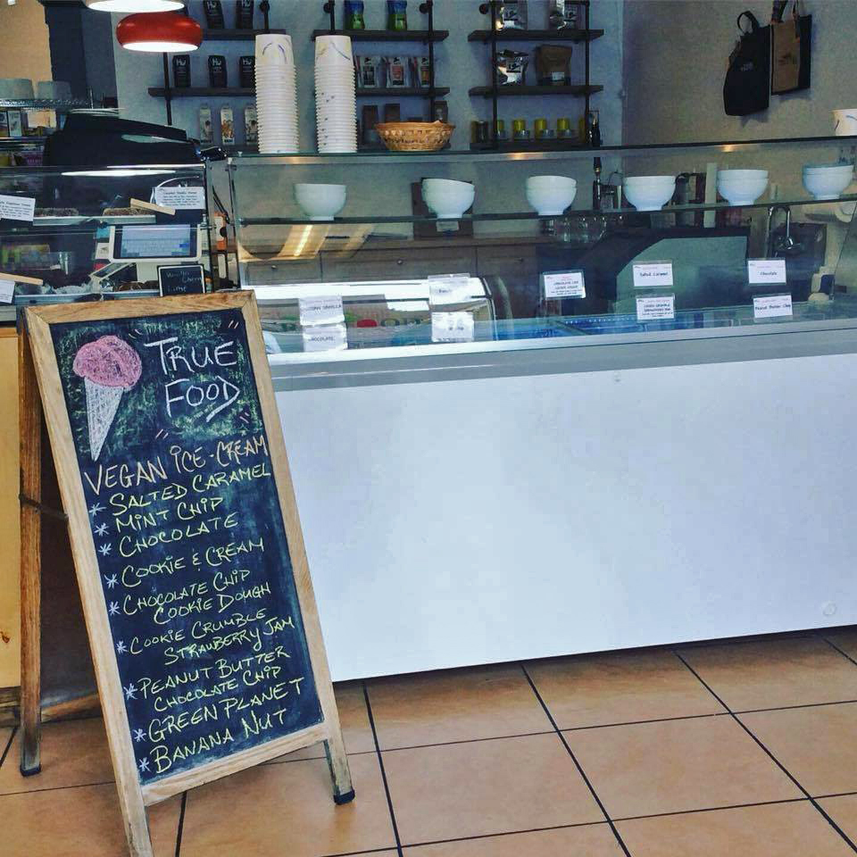 The font counter of the coffee and cream shop which includes a chalkboard that lists all the vegan ice cream options