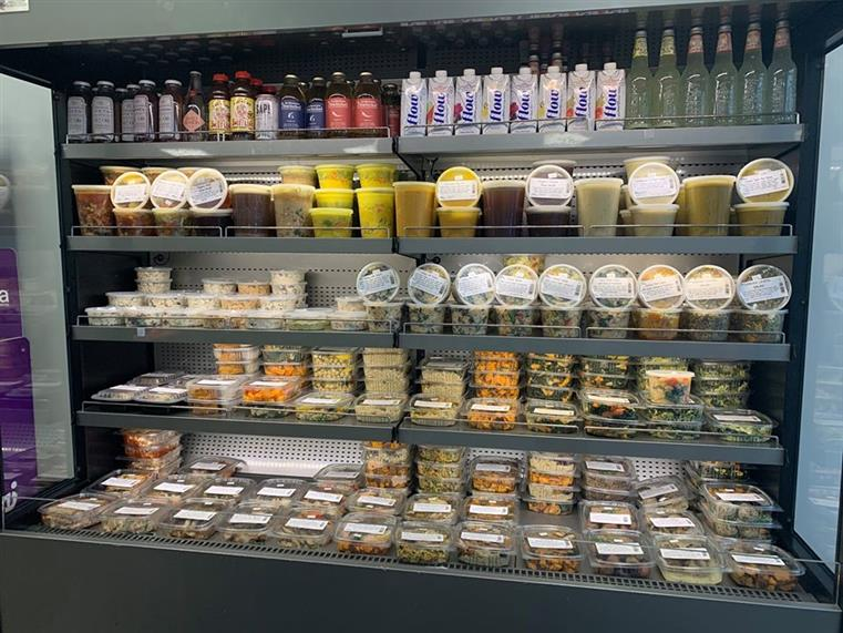 Refrigerated shelves of market inventory, which includes fresh juices, and meals in to-go containers