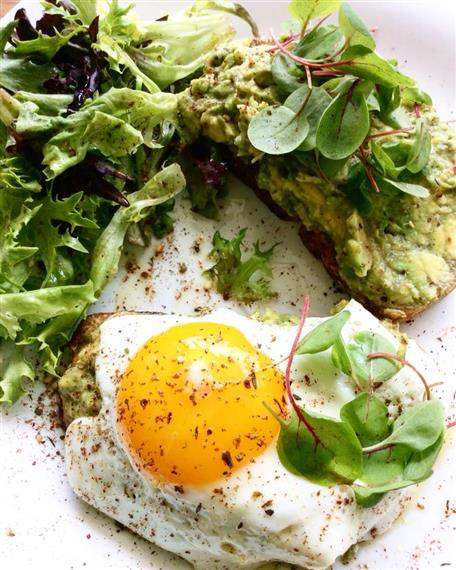 Eggs over a bed of lettuce with avocado toast