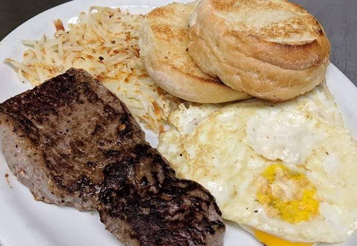 steak and eggs plate with hash browns and biscuits