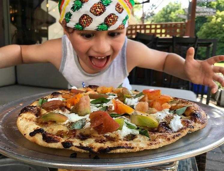 little boy who is enthusiastic about the pizza in front of him
