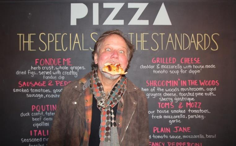 Man posing for photo with a slice of pizza in his mouth