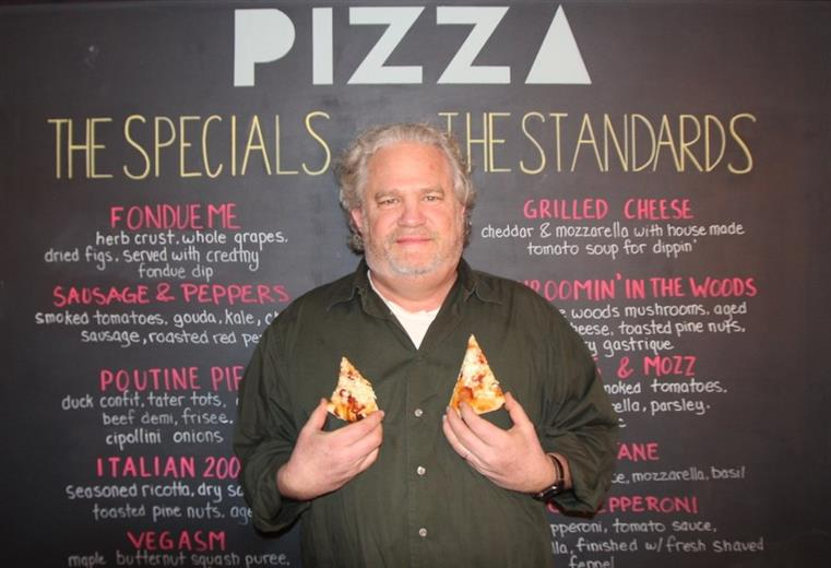 A man holding two small slices of pizza posing for a photo