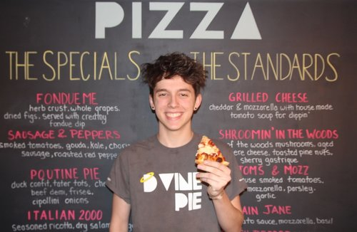 boy posing for a photo with a slice of pizza in his hand