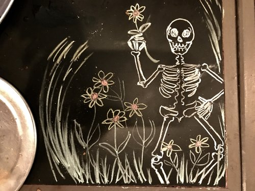 chalk art of a skeleton holding a flower