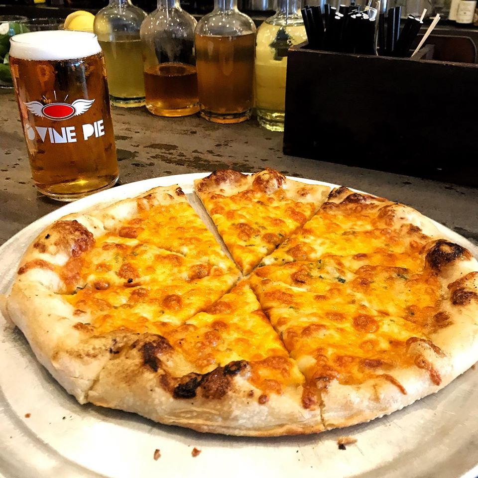cheese pizza on a tray with a glass of beer