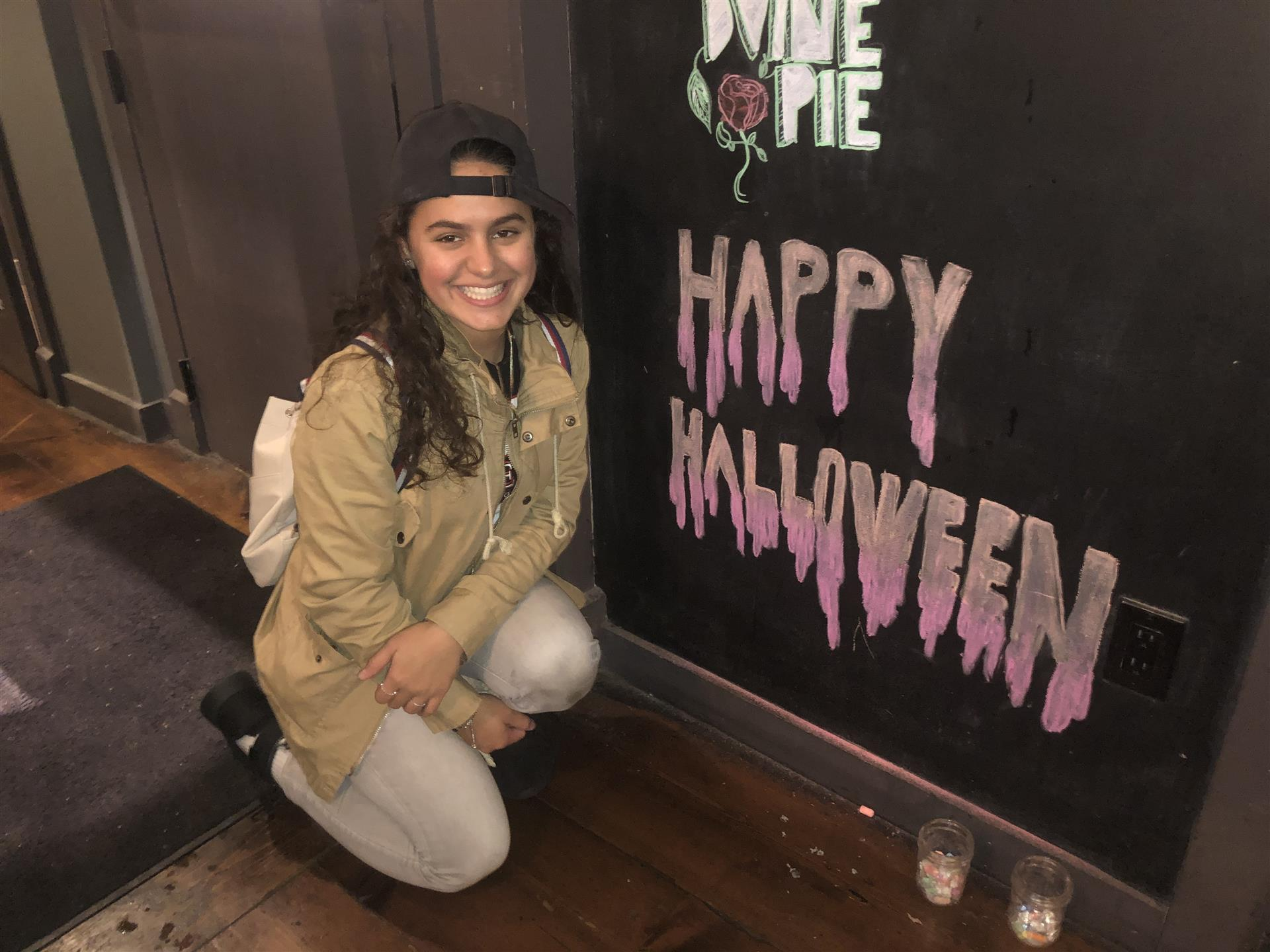 woman posing in front of chalk board