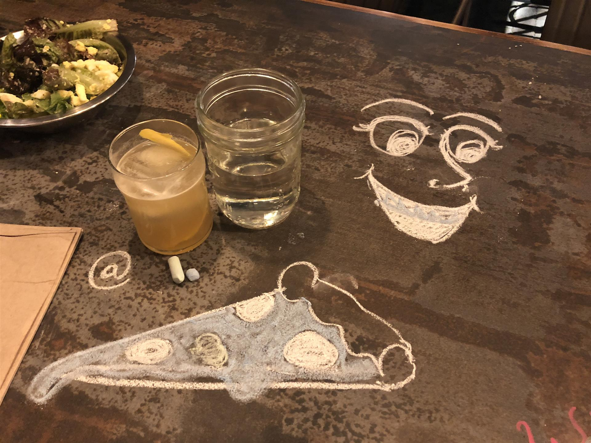 chalk art of a face and a slice of pizza with two drinks on the table