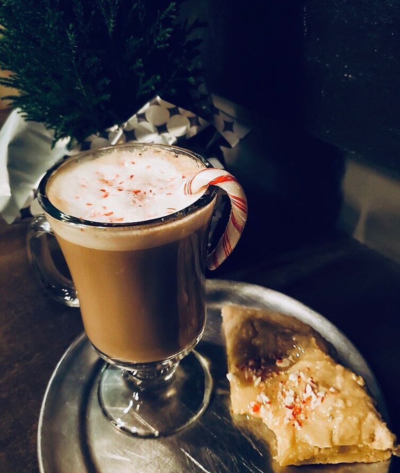 iced coffee with a candy cane hanging on the side and a slice of pizza with a bite