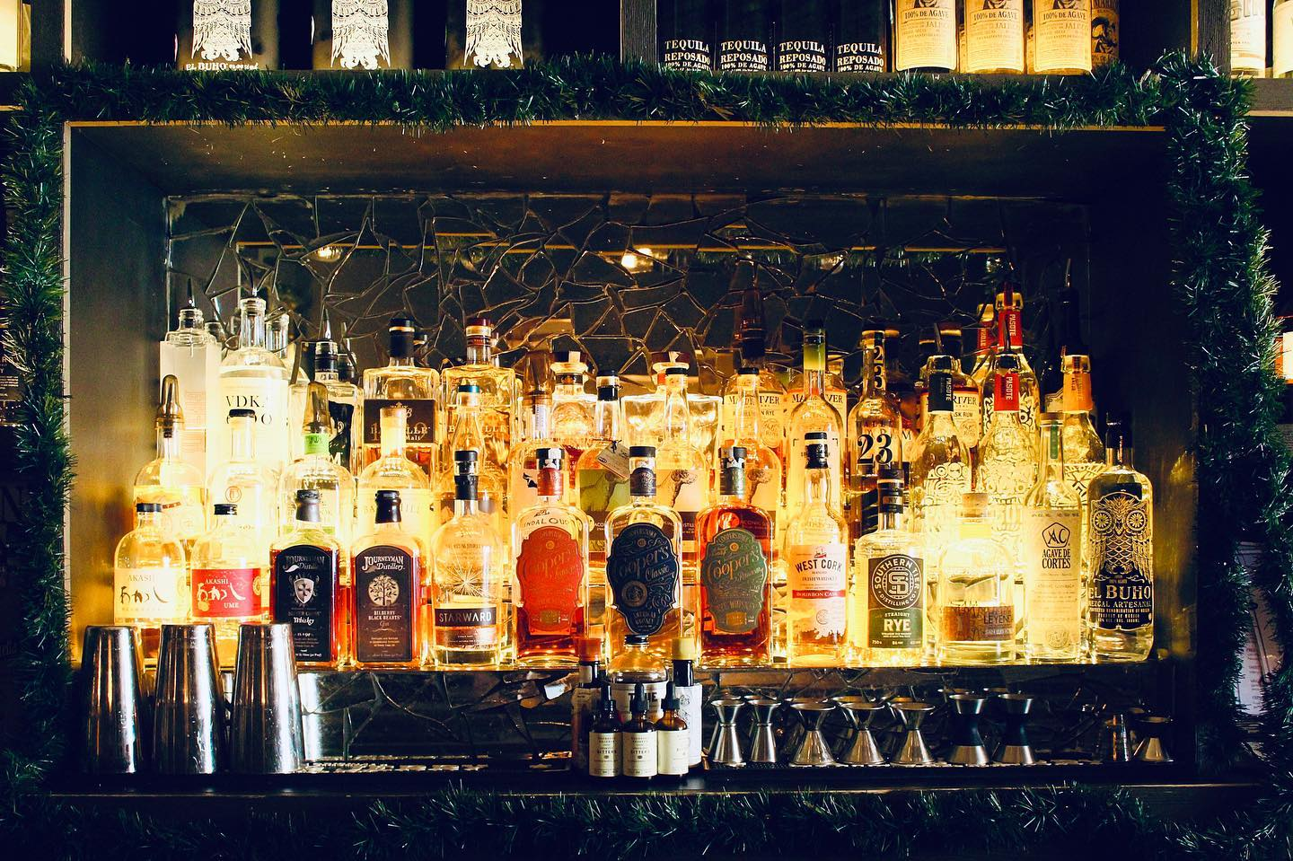 assortment of alcoholic bottles in bar area