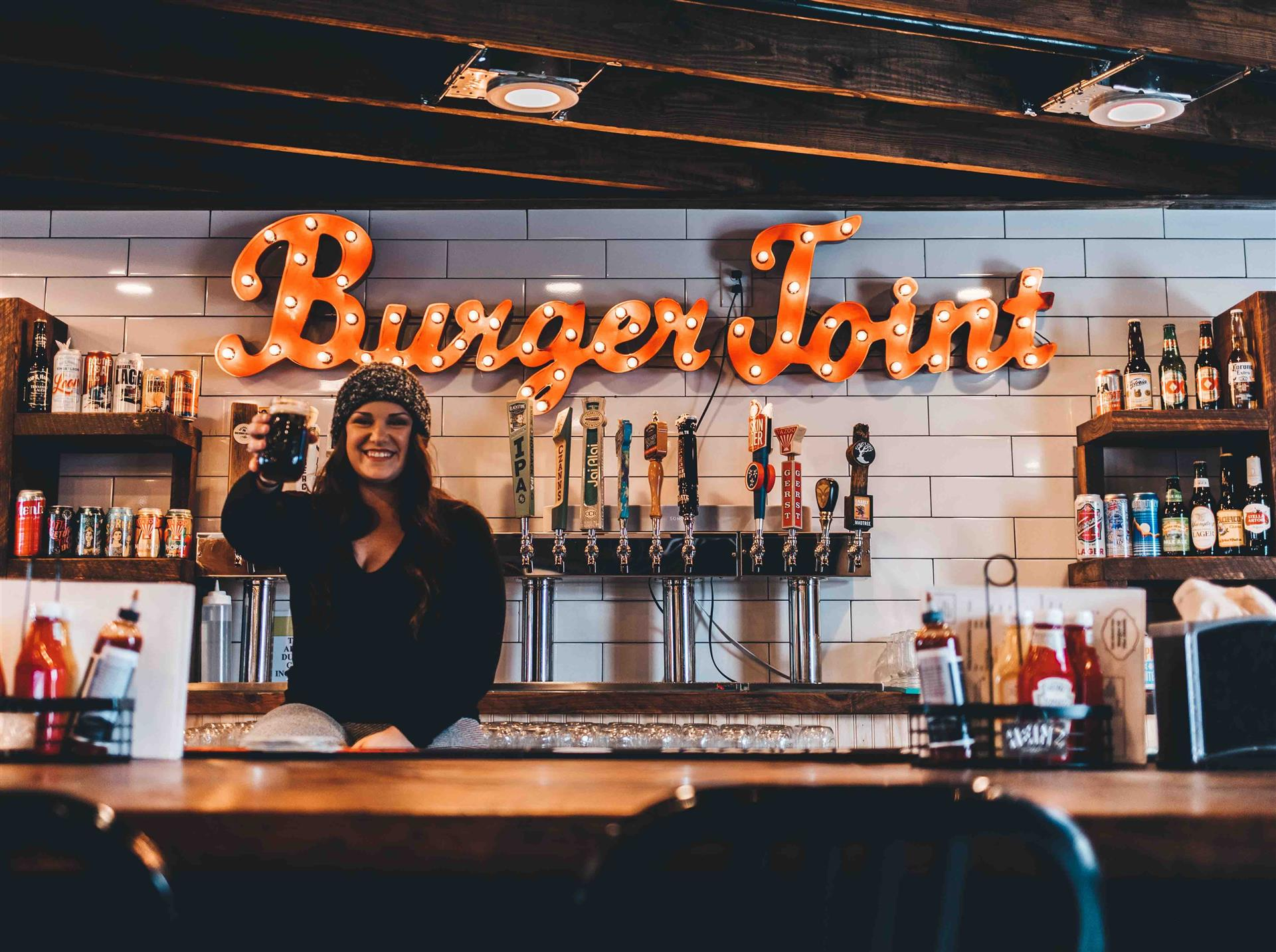 bartender behind the bar raising a drink with view of beer taps behind her and a Burger Joint sign on the wall