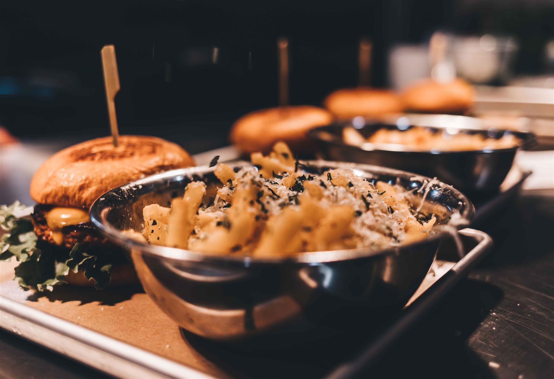 bowls of truffle fries served on platters with specialty burgers