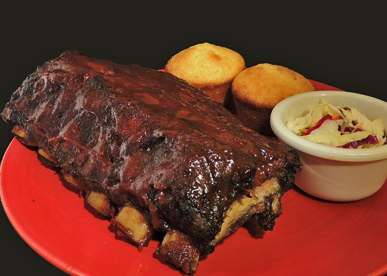 A rack of BBQ ribs on a plate with a side of coleslaw and 2 corn muffins