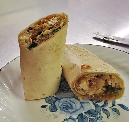A chicken and rice wrap with tomatoes and spinach