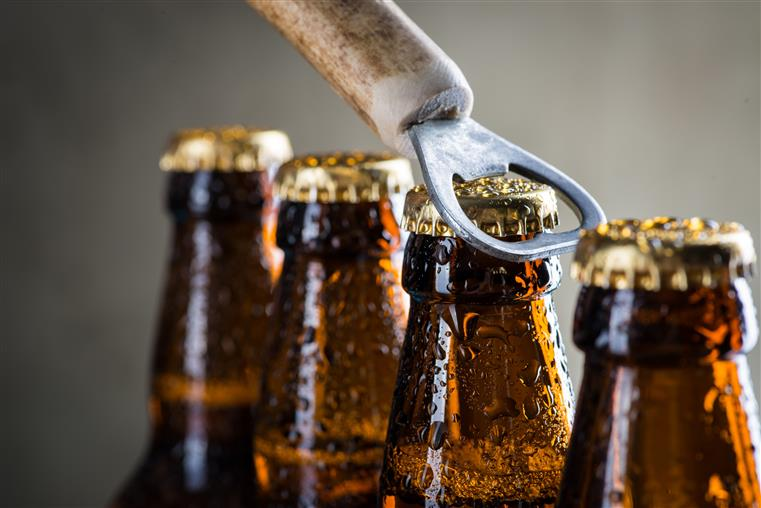 beer bottles lined up being opened