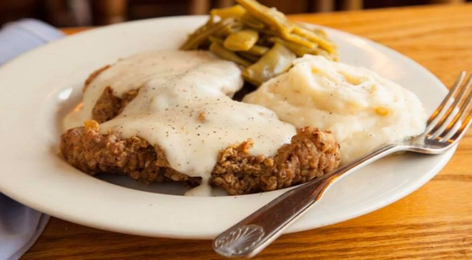 chicken fried steak with green beans, mashed potatoes and a creamy pepper gravy