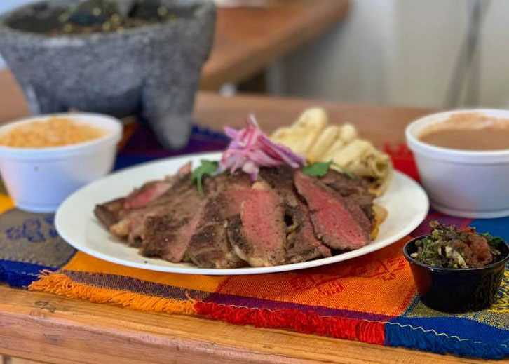Sliced steak on a plate, topped with pickled onion