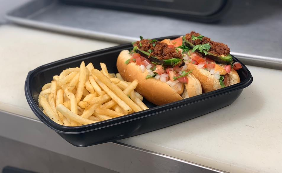 sausage on a roll topped with onions, tomatoes, cilantro, jalapenos, shredded beef and a side of French fries