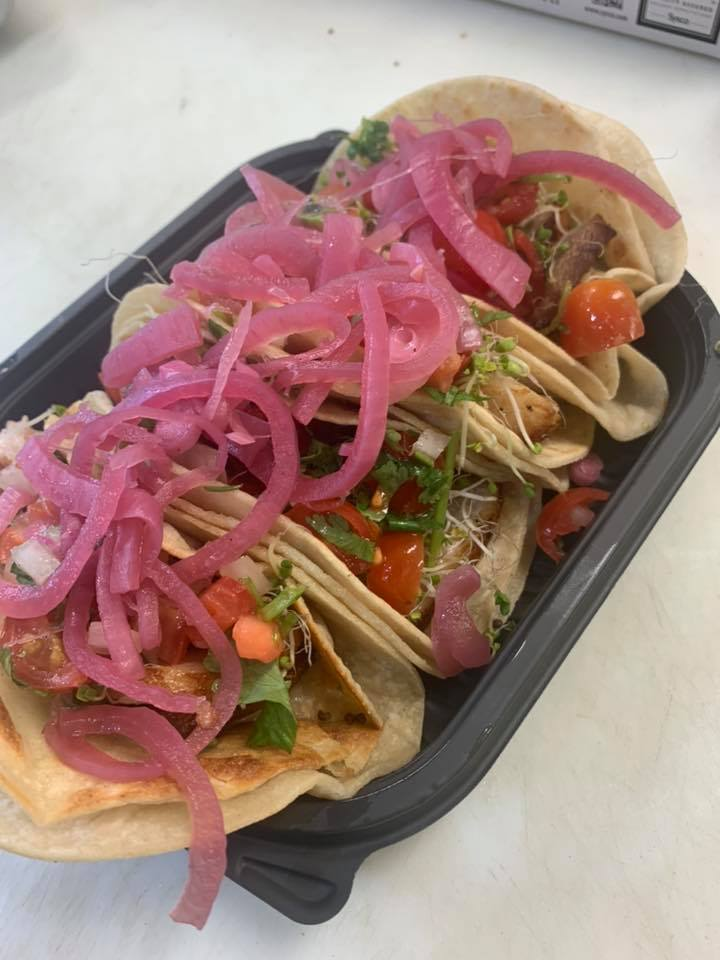 4 tacos in corn tortillas topped with pickled red onion, cilantro and tomato
