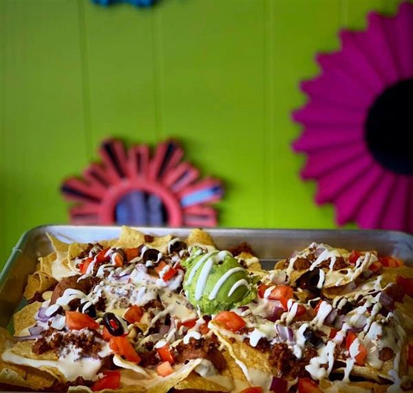 Nachos topped with beef, tomatoes, olives, cheese, sour cream, and guacamole