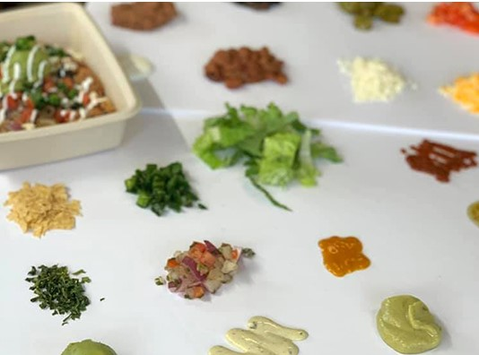 table of toppings with lettuce, sauces, cilantro, pico de gallo, cheese, and beans