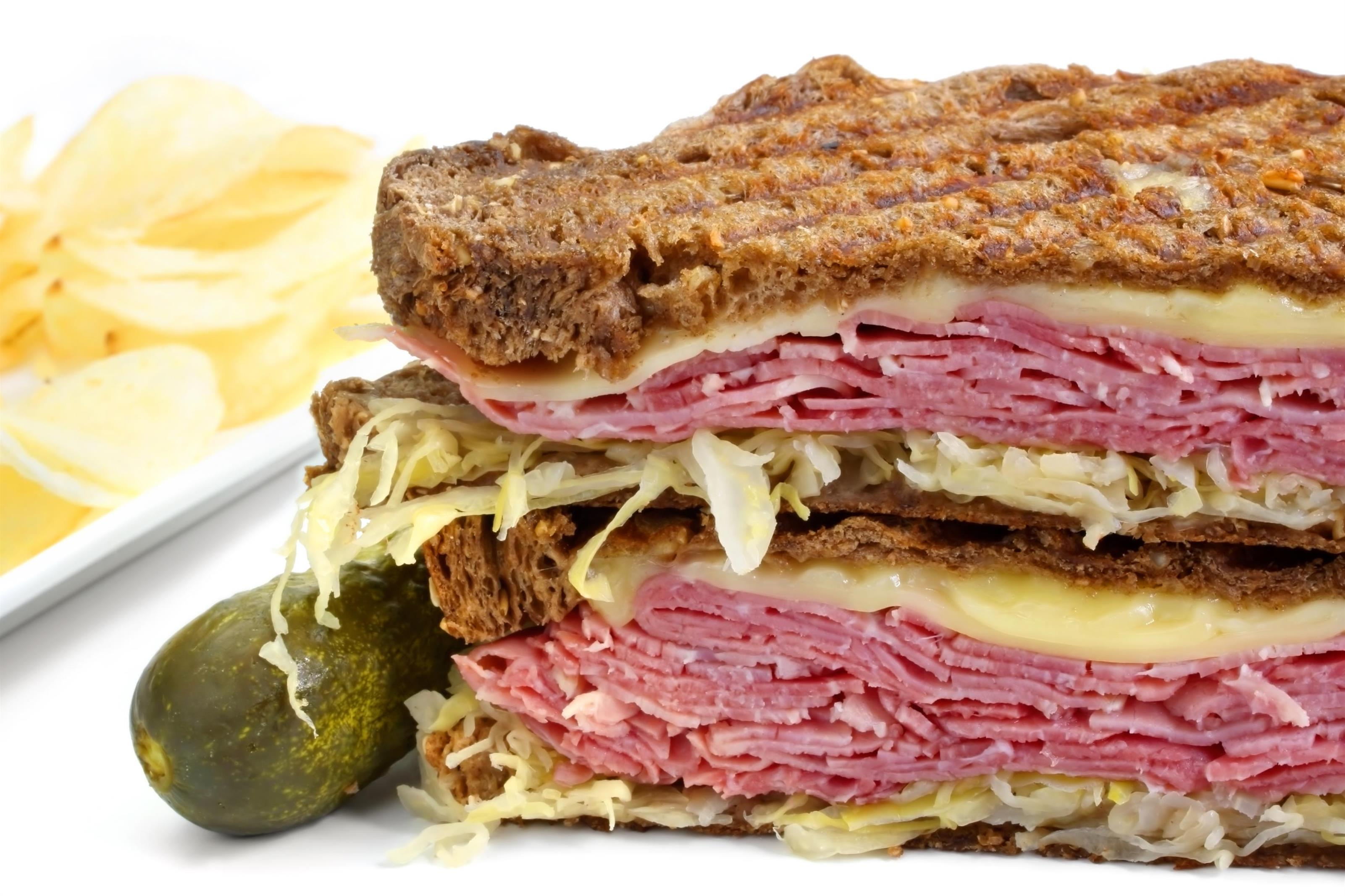 reuben sandwich with corned beef, coleslaw, and cheese on a toasted panini sandwich with pickles on the side