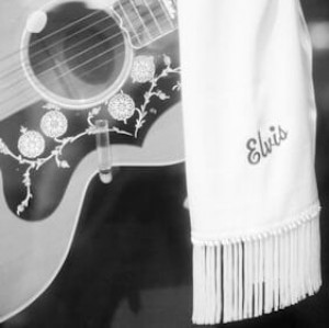"guitar with a scarf hanging over that says ""Elvis"""