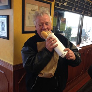 man inside the restaurant biting into a sub sandwich