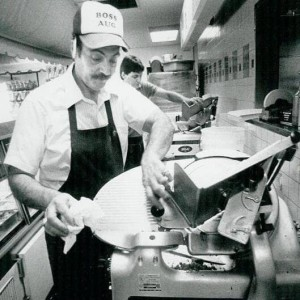 old photo of Augie as the chef in the kitchen using the meat slicer