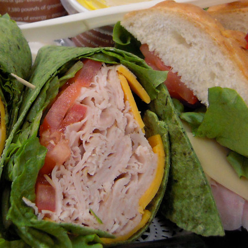 ham, cheese, tomatoes and lettuce wrapped up in a spinach wrap