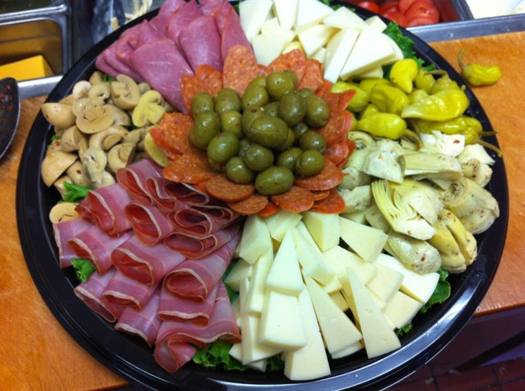 various meats and cheeses on a tray with olives, artichokes, pepperoncini and mushrooms