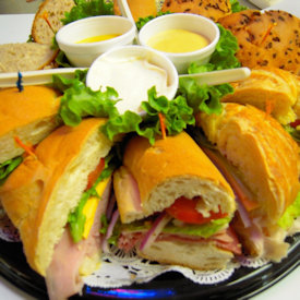 assorted sub sandwiches on a tray with different dipping sauces on the side