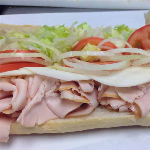 sub sandwich being made with turkey, provolone cheese, onions, shredded lettuce, tomatoes, and mustard